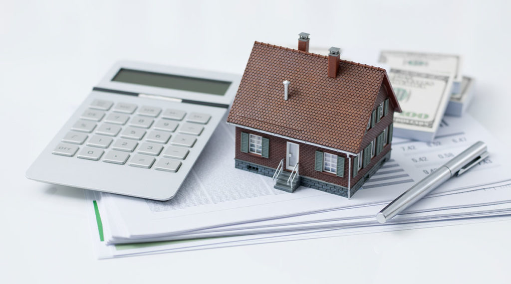 photo of house on top of calculator to talk about selling inherited property quickly in 2021 - quick home buyers nj